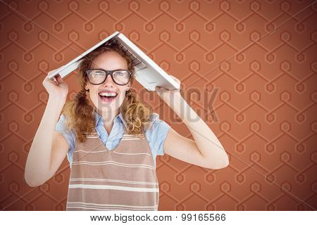 Geeky hipster woman covering her head with her laptop against background