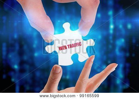 The word web traffic and hands holding jigsaw against digitally generated black and blue matrix