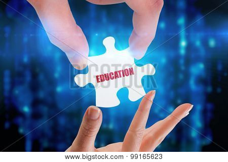 The word education and hands holding jigsaw against digitally generated black and blue matrix