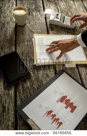 Businessman Calculating Sales On The Table