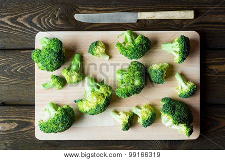 Fresh green broccoli on cutting board over rustic wooden background. Healthy or vegetarian food concept