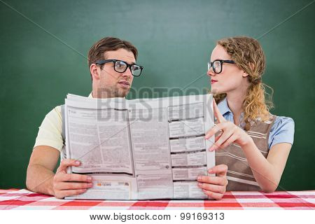 Geeky hipster couple reading newspaper against green chalkboard