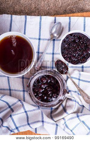 Blackberry jam jar and cup of tea over linen napkin, top view
