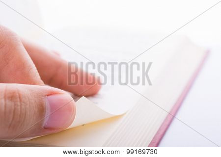 Close-up shot of male fingers turn new page of a book