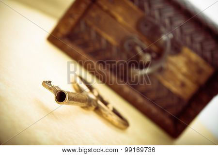 Close-up shot of old metal key and closed wooden treasure chest