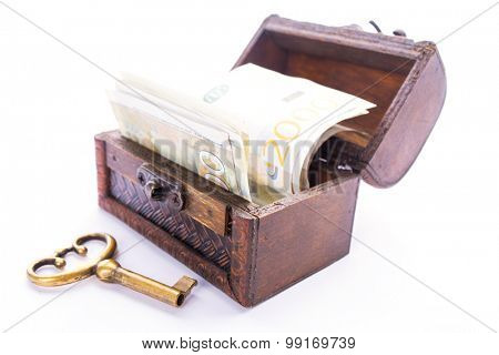 Old metal key and Serbian money in a wooden chest, isolated on white