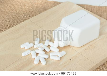 Many White Pills / Tablets / Medicine On Wood Plate
