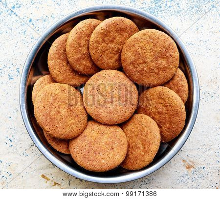 A collection of ginger flavoured cookies kept on a bowl on a plain background