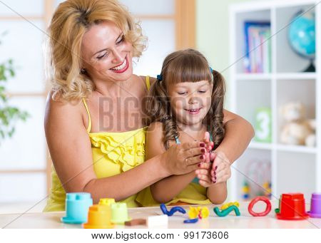 mom and daughter play colorful clay toys at home