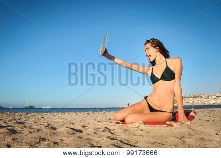 Young girl taking a selfie with a tablet while sitting on the sand
