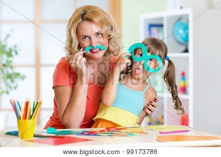 Child with mother have a fun cutting out scissors paper in preschool