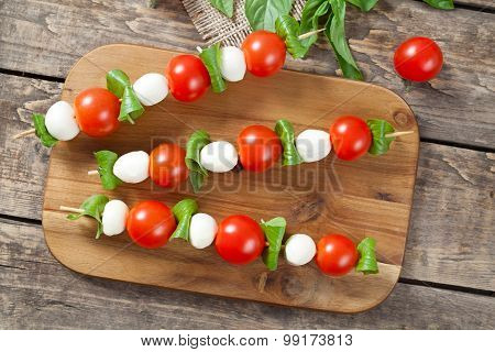 Italian traditional homemade skewers with mozzarella tomatoes and basil called caprese on wooden des