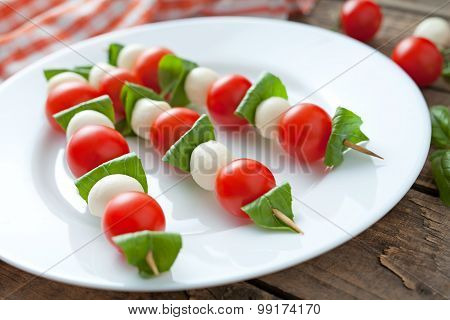 Mozzarella basil and tomatoes skewers on wooden sticks called caprese salad natural organic antipast