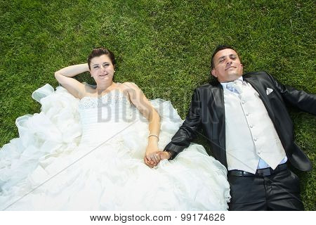 Bride And Groom Holding Hands On Lawn