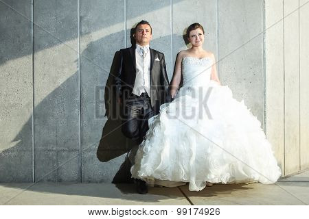 Bride And Groom Posing In Front Of Wall