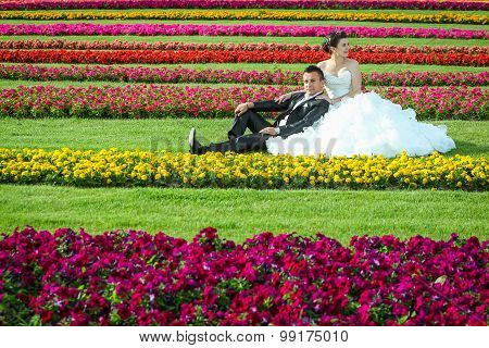 Bride And Groom Sitting On Lawn With Flowers