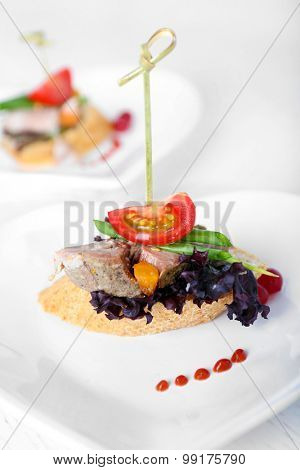 Tasty canapes on wooden table, close up