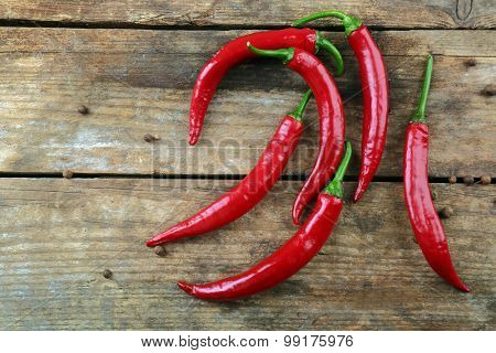 Red hot peppers with spices on wooden table close up