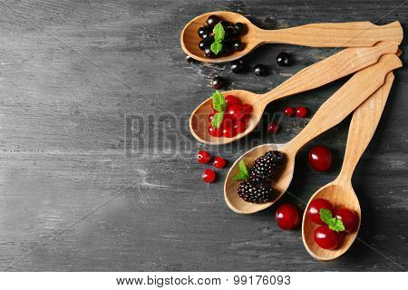 Forest berries in wooden spoons on color background