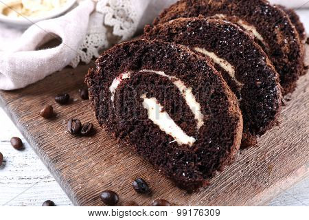 Delicious chocolate roll on wooden cutting board, closeup