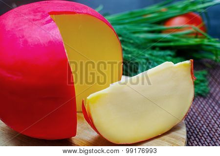 Edam Cheese And A Piece On Cutting Board