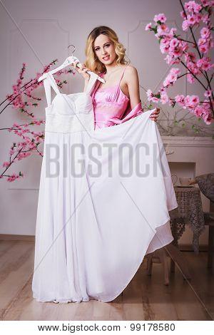 Blond Beautiful Woman Holds Her Wedding Dress