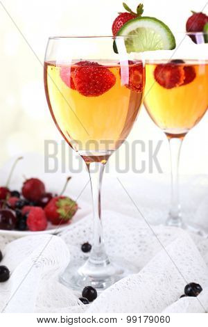 Glasses of wine with strawberries and slice of lime on light background