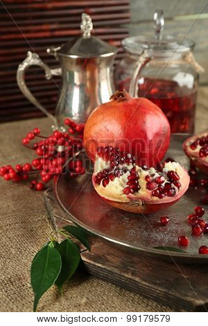 Pomegranate seeds and juice on metal tray and sackcloth, closeup
