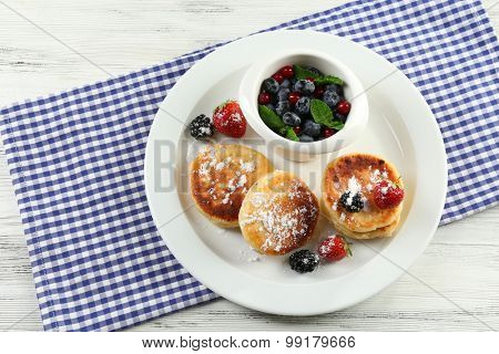 Fritters of cottage cheese with berries in plate on table, closeup