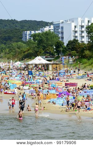 MIEDZYZDROJE - AUGUST 16: Tourists enjoy the sunny weather and relaxing on the Baltic sea beach on 16 August 2015 in Miedzyzdroje, Poland.