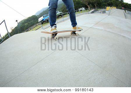 closuep of skateboarder legs riding skateboard  at skatepark