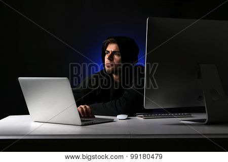 Hacker with computer and laptop on dark background