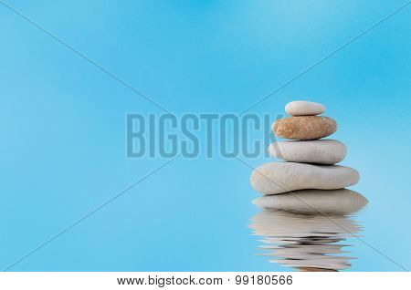 Stacked Stones With Watery Reflection Against Blue Sky