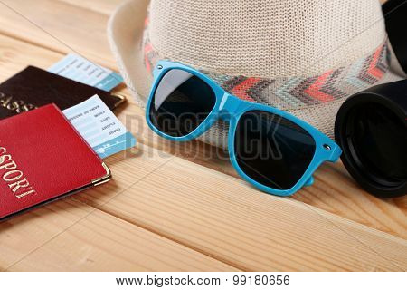 Sunglasses, passports and tickets, close up, on wooden background. Preparing for travel concept