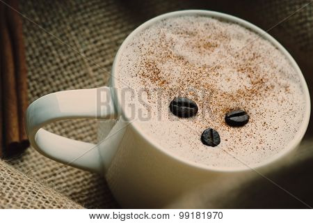 Coffee cup,coffee beans and cinnamon on burlap sack