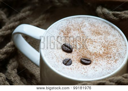 Coffee cup,coffee beans and rope on burlap sack