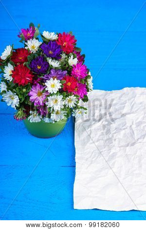 Flower bouquet in vase and sheet of paper