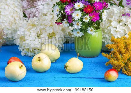 Flowers and fruits on a wooden table