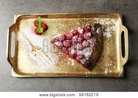 Piece of cake with Chocolate Glaze and raspberries on tray, on dark background