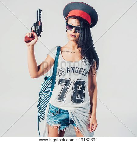 Fashion swag sexy girl holding toy gun woman having fun wearing police cap.