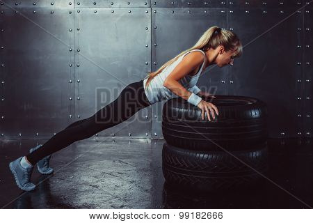 Sportswoman. Fit sporty athlete woman doing push ups on tire strength power training concept crossfi