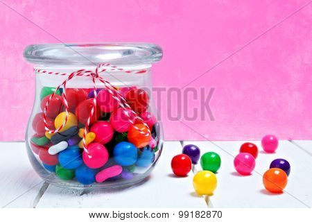 Candy jar of gum balls on pink background