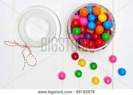 Open candy jar filled with gum balls on white wood
