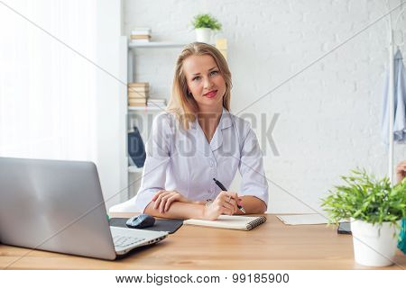 Medical doctor woman sitting at desk in medical office.