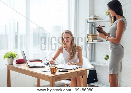 Two young woman working together in office businesswoman having serious conversation with collegue.