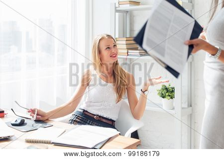 Young woman sitting on chair in office working and talking with collegue