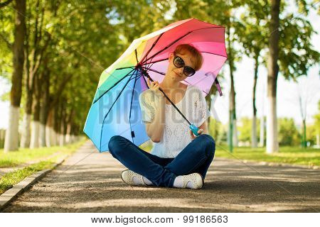 Girl With Multicolored Umbrella Is Sitting On Sidewalk