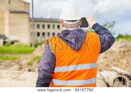 Construction inspector filming with tablet PC near building