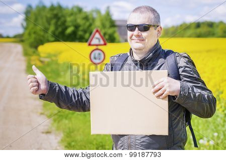 Hiker with cardboard try to stop car on rural road