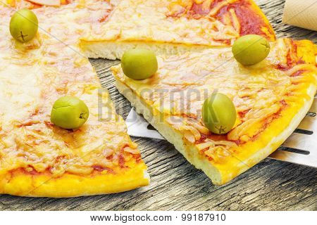 Pizza with ham and green olives on table